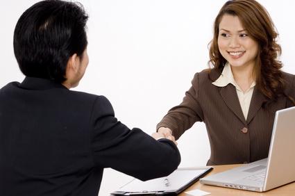 Deux personnes se saluent lors d'un premier entretien. L'une, de face cherche à donner une bonne impression: salutations d'entrée, poignée de main ferme, sourire agréable, ...