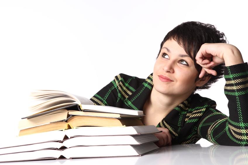 Une jeune femme rêve, délaissant ses livres d'école.
