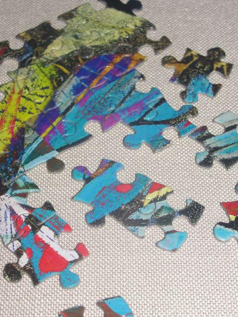 Pièces d'un puzzle en train d'être assemblées; étape difficile pour marier les formes, couleurs et motifs.