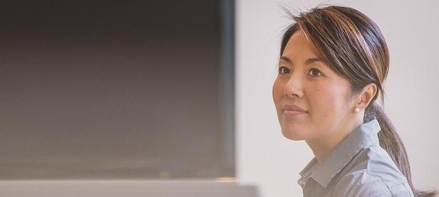 une femme redresse la tête ave can visage détendu et souriant devant un tableau noir
